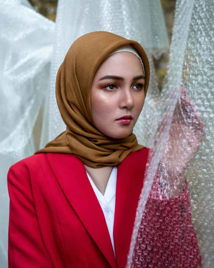 photo of woman wearing hijab while standing near bubble wrap