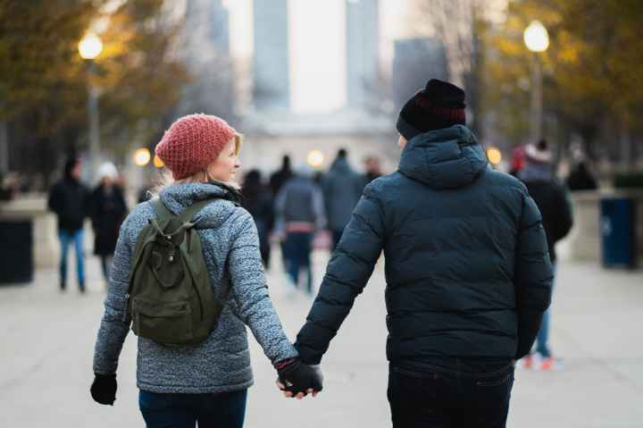 man and woman holding hands while walking at park