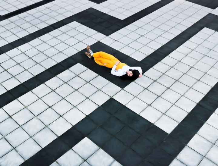 woman in yellow pants lying on concrete tiled floor
