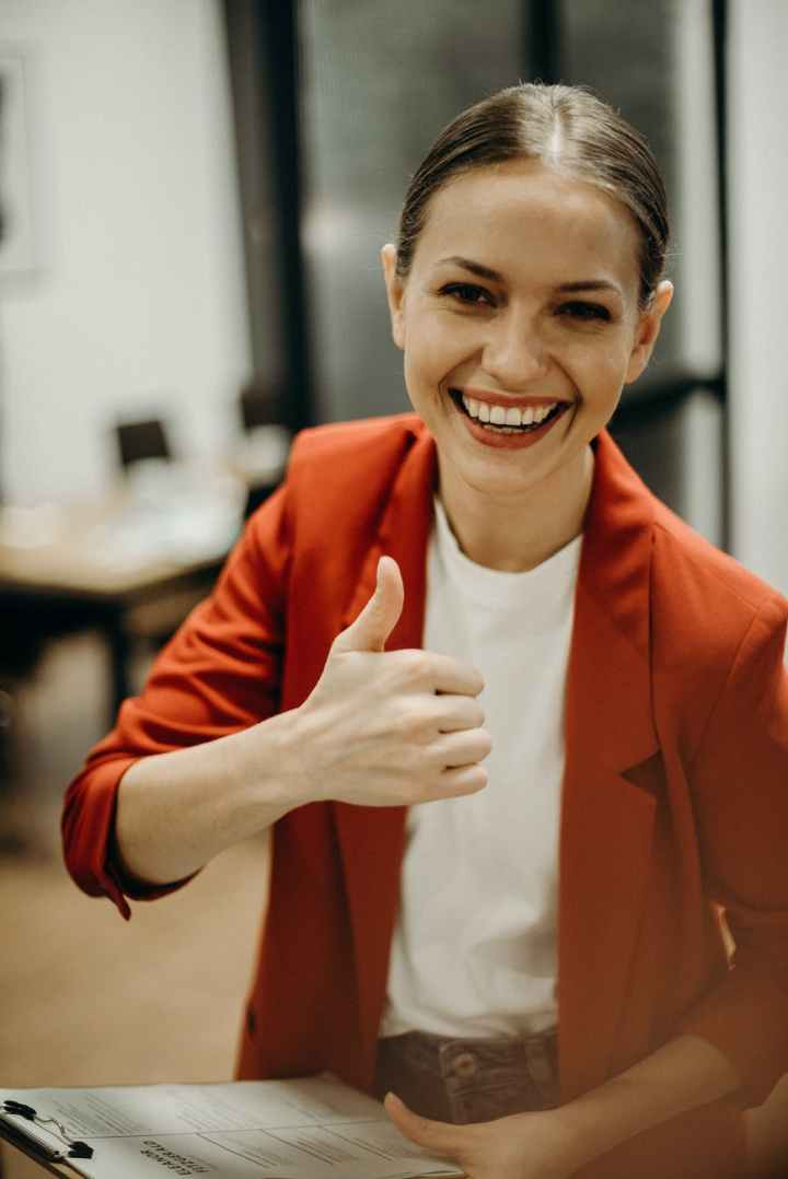 woman wearing orange blazer showing thumbs up
