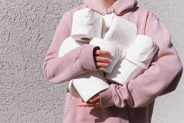 woman in pink long sleeve hoodie carrying tissue rolls