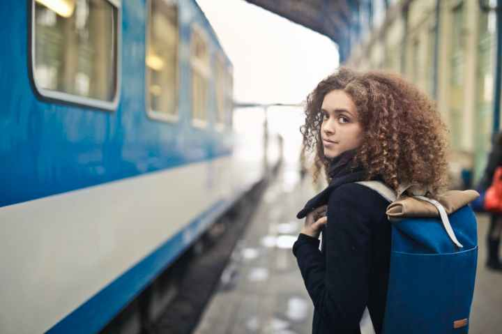 woman in black coat standing beside blue and white train